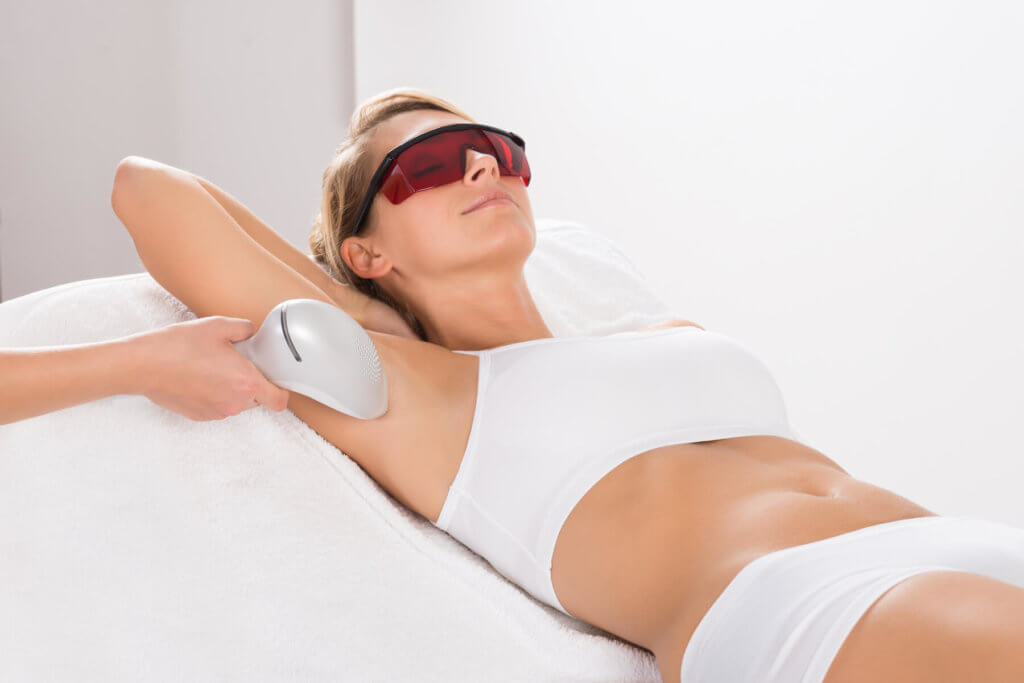 A woman receiving laser hair removal on her underarms.